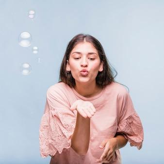Menina morena brincando com bolhas de sabão