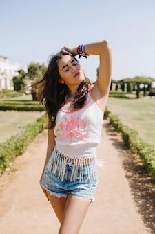 Menina morena bronzeada com roupa da moda, andando pela rua com uma expressão de rosto sonhadora. retrato de uma jovem bonita com cabelo castanho brilhante, vestindo uma camiseta retrô, aproveitando as férias de verão no parque