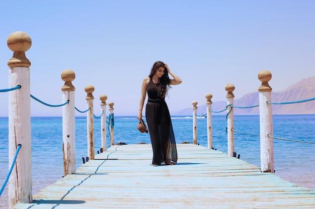 Menina morena caminhando na ponte de madeira com vista para o mar e as montanhas