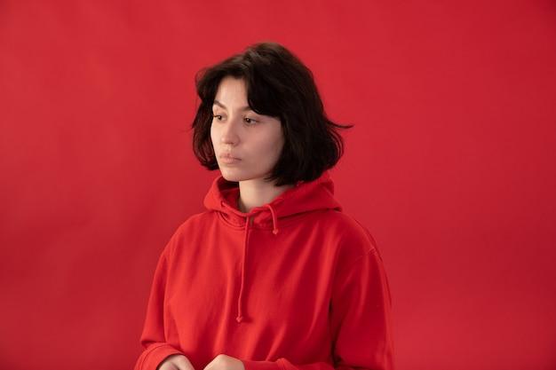 Menina morena cansada com capuz vermelho posando
