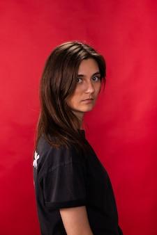 Menina morena cansada de cabelos compridos em camiseta preta olhando para frente no estúdio vermelho