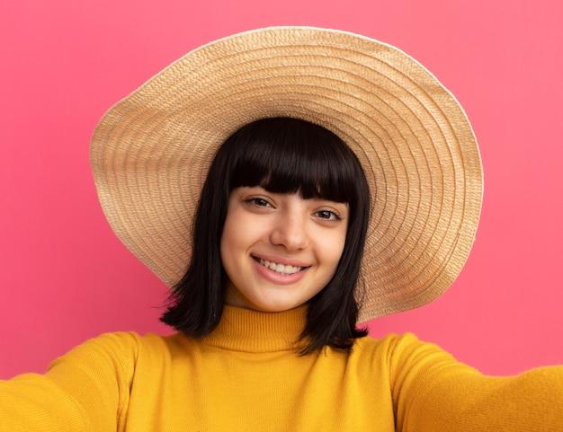 Menina morena caucasiana sorridente com chapéu de praia finge segurar a câmera, tirando uma selfie isolada na parede rosa com espaço de cópia