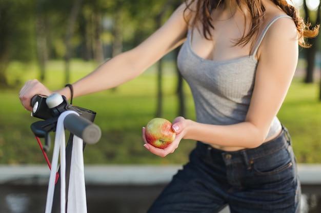 Menina morena closeup com sua scooter elétrica em um parque, segurando uma maçã na mão closeup