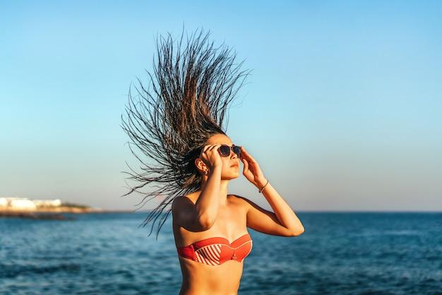 Menina morena, com, cabelo fluindo, sunbathing, ligado, a, pedras, em, a, mar