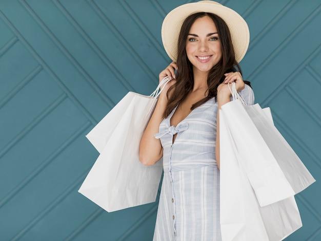 Menina morena com chapéu e muitas redes de compras