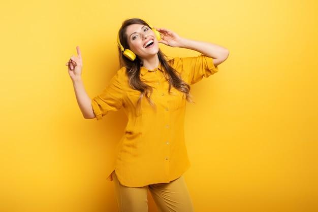 Menina morena com fone de ouvido amarelo ouve música e dança