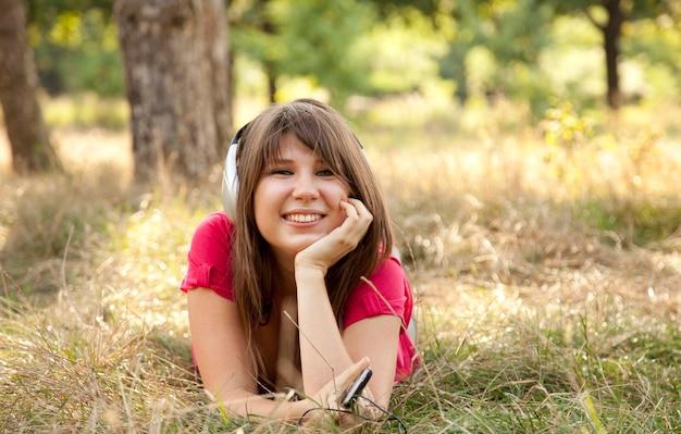 Menina morena com fone de ouvido no parque.