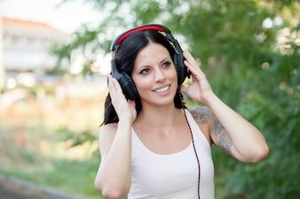 Menina morena com fones de ouvido andando
