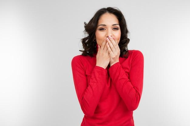 Menina morena com um suéter vermelho justo esconde um segredo, fechando a boca com a mão em um fundo branco com espaço de cópia