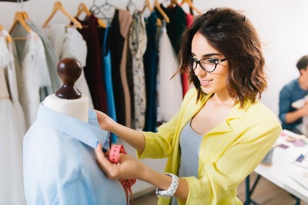 Menina morena com uma jaqueta amarela faz a camisa adequada no manequim. ela trabalha em um ateliê. há muitas roupas no fundo.