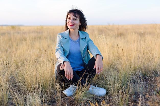 Menina morena com uma jaqueta azul deitada em um campo na grama amarela y