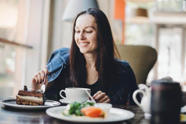 Menina morena comendo bolo no restaurante. aproveitando a comida