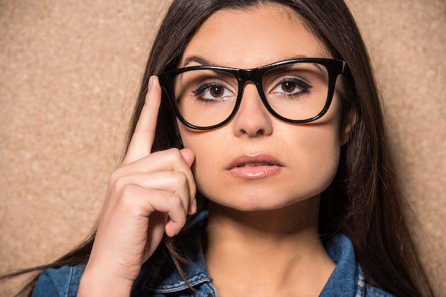 Menina morena de beleza de óculos com cabelos longos.
