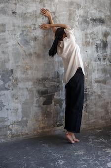 Menina morena de blusa branca e calça jeans preta fica na ponta dos pés