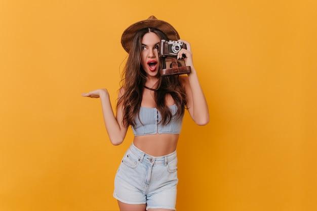 Menina morena de cabelos compridos entusiasmada com um chapéu segurando uma câmera e expressando emoções positivas