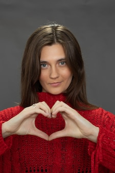 Menina morena de cabelos compridos fazendo um gesto de coração com o dedo olhando para a frente