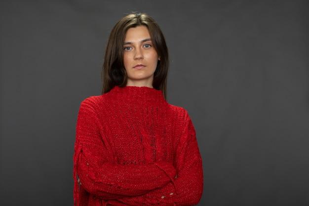 Menina morena de cabelos compridos, muito calma, posando com os braços cruzados em um suéter vermelho