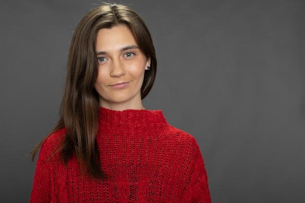 Menina morena de cabelos compridos posando com um suéter vermelho olhando para a frente