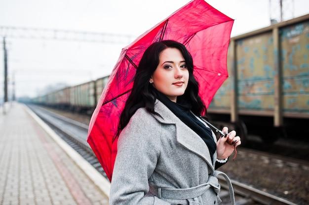 Menina morena de casaco cinza com guarda-chuva rosa na estação ferroviária