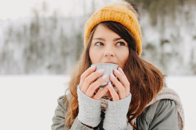 Menina morena de chapéu de malha amarelo com caneca de metal de chá quente na floresta ao ar livre no inverno