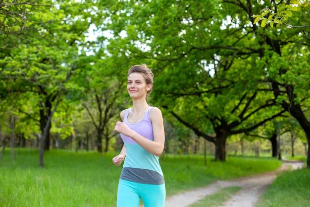 Menina morena de esportes, movimentando-se no parque. floresta verde no fundo