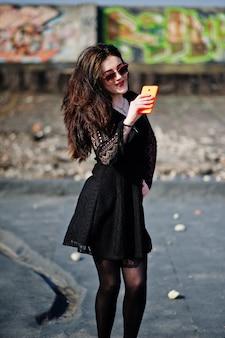 Menina morena de retrato com lábios vermelhos e laranja celular nas mãos, usando um vestido preto, óculos de sol colocados no telhado