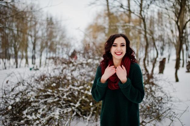 Menina morena de suéter verde e lenço vermelho ao ar livre na noite dia de inverno.