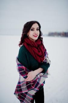 Menina morena de suéter verde e lenço vermelho com lago congelado ao ar livre xadrez na noite dia de inverno.