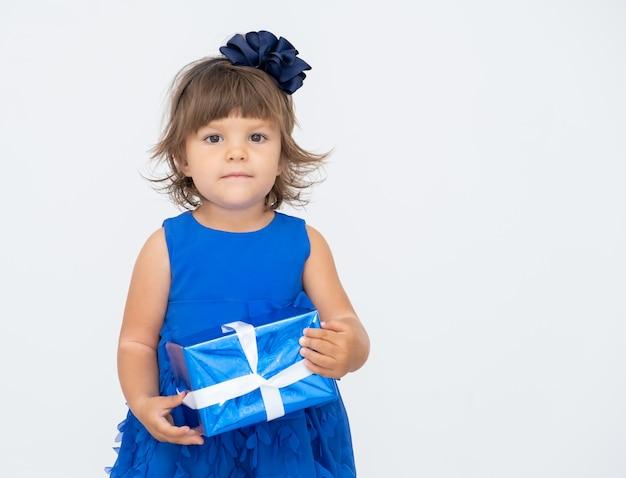 Menina morena de vestido azul segurando uma caixa de presente