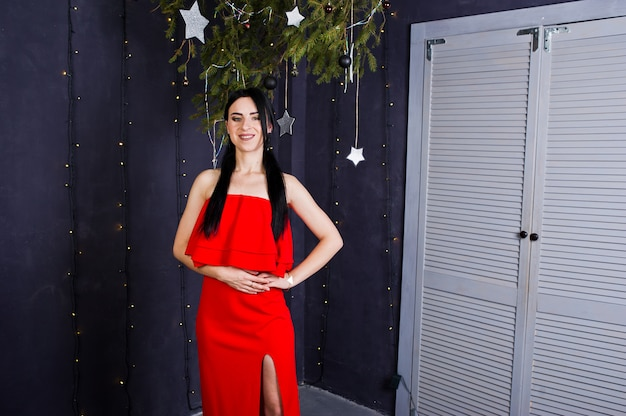 Menina morena de vestido vermelho posou perto de decoração de ano novo na sala de estúdio.