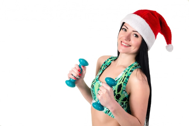 Menina morena desportiva no chapéu de papai noel fazendo exercícios com halteres.