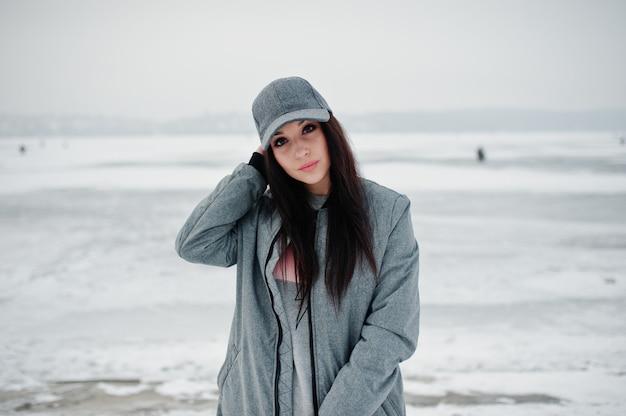 Menina morena elegante boné cinza em dia de inverno.