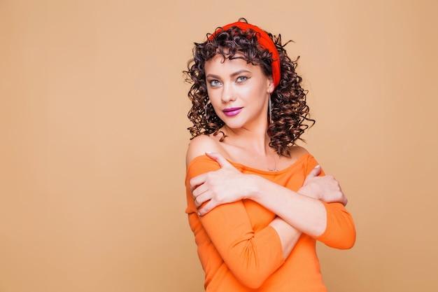 Menina morena elegante com um suéter laranja brilhante e uma bandana posando em laranja