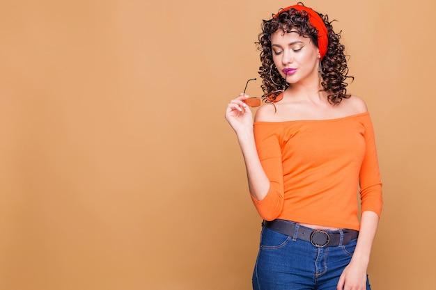 Menina morena elegante com um suéter laranja brilhante, óculos e uma bandana posando em laranja
