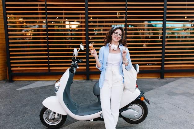 Menina morena elegante de óculos e jaqueta azul tomando sorvete depois das compras