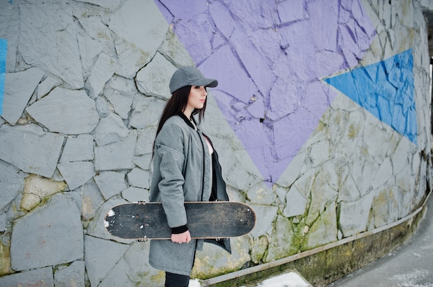 Menina morena elegante em capwith cinza skate