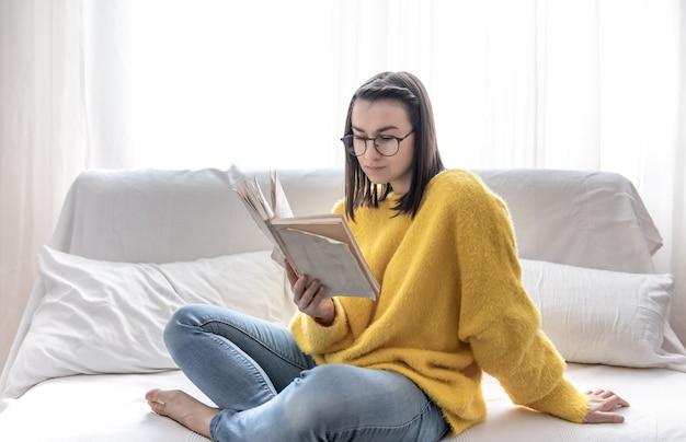 Menina morena elegante em um suéter amarelo e óculos lê um livro em casa no sofá. o conceito de autodesenvolvimento e relaxamento.