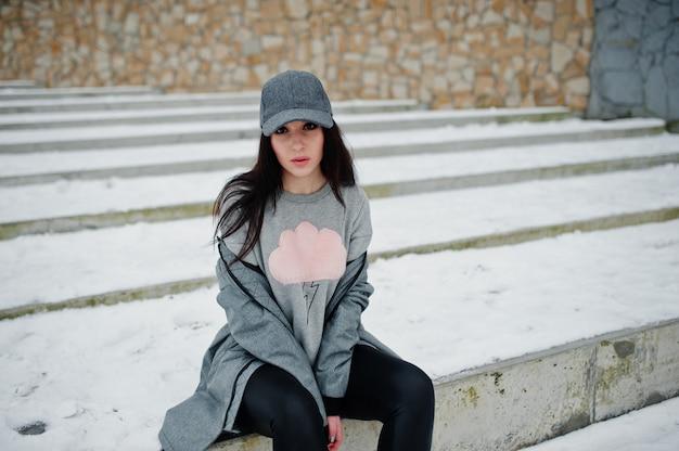 Menina morena elegante no boné cinza
