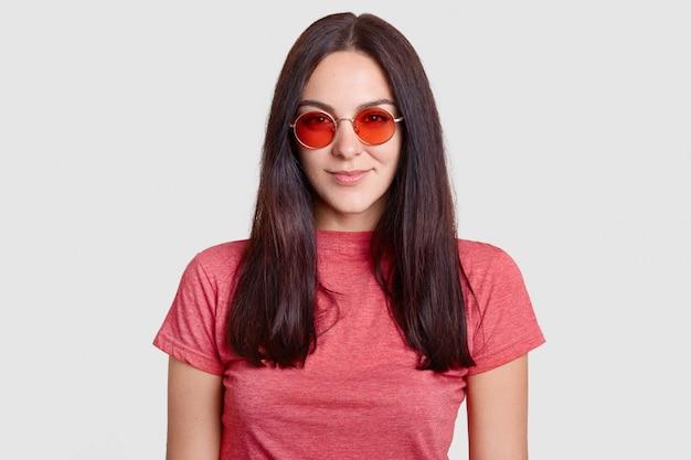 Menina morena elegante usa óculos de sol redondos vermelhos na moda, camiseta casual, pronta para passear durante o dia de sol