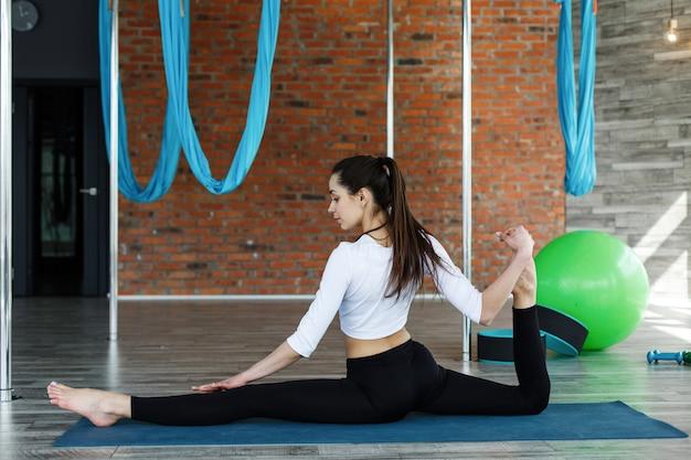 Menina morena em roupas esporte preto e branco faz ioga e alongamento no ginásio