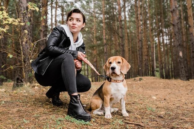 Menina morena em trajes casuais sentada no agachamento durante o relaxamento com cachorro beagle puro-sangue na floresta no dia de outono