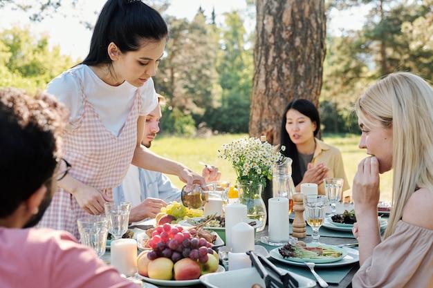 Menina morena em trajes casuais servindo bebida em um copo enquanto se curva na mesa servida entre seus amigos durante o jantar ao ar livre