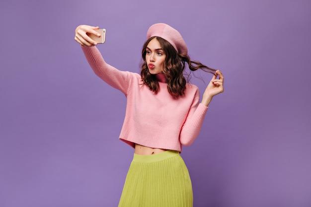 Menina morena encantadora tocando cabelo, segurando smartphone e tirando selfie