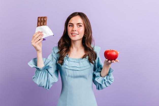 Menina morena encaracolada de olhos verdes posando com maçã vermelha e barra de chocolate ao leite na parede roxa.