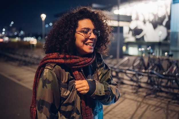 Menina morena encaracolada sorrindo na rua