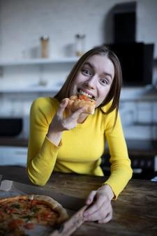 Menina morena engraçada com suéter amarelo comendo pizza na cozinha