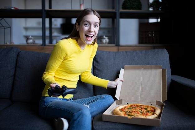 Menina morena engraçada de suéter amarelo comendo pizza em casa. entrega de pizza