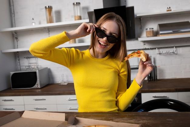 Menina morena engraçada de suéter amarelo e óculos escuros comendo pizza na cozinha