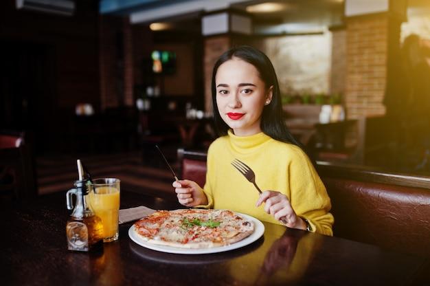 Menina morena engraçada na camisola amarela que come a pizza no restaurante.