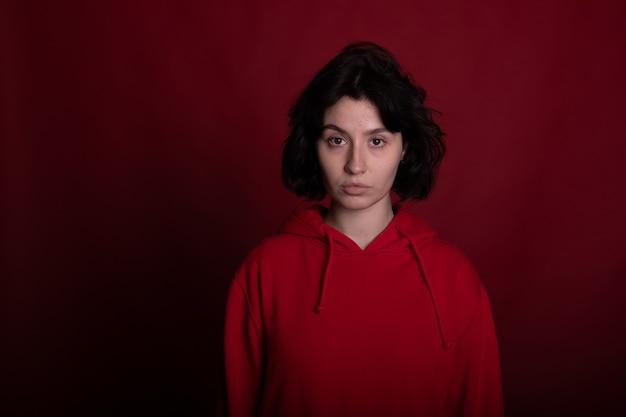 Menina morena exausta com um capuz vermelho posando no fundo escuro do estúdio